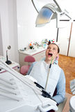 Woman in dentist chair Stock Images