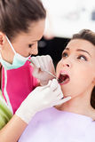 Woman dentist checking her patient Royalty Free Stock Images