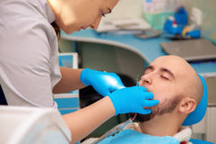 Woman dentist checks the teeth of her patient in the dental offi Stock Photos