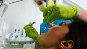 Woman dentist curing ladys teeth, doctor providing dental services, medicine. Stock photo stock photos