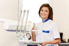 Woman dentist with dental tools. Young brunette woman dentist with dental tools in dentist's surgery Royalty Free Stock Photo