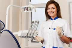 Woman dentist with dental tools. Young brunette woman dentist with dental tools in dentist's surgery Stock Images