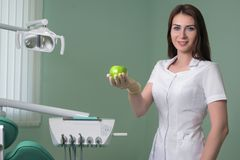 Woman dentist doctor in the dental office holding a green Apple. royalty free stock image
