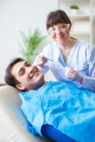 The woman dentist doctor with male patient in hospital stock image