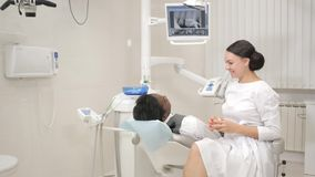 Woman dentist examines and consults the patient. Young African American male patient at chair at dental clinic. Medicine. Young beautiful girl doctor dentist stock video
