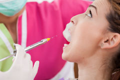 Woman dentist giving her patient an anesthesia injection Royalty Free Stock Photography
