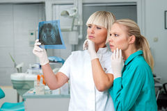Woman dentist with her assistant. Women dentist and her assistant looking at x-ray image and thinking Stock Photography