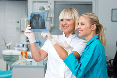 Woman dentist with her assistant. Women dentist and her assistant looking at x-ray image and smiling Stock Photos
