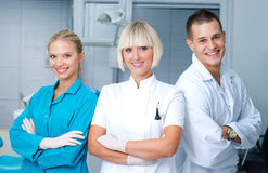 Woman dentist with her assistants. Women dentist standing in office with her personal assistants crew stock images