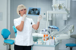 Woman dentist looking x-ray image Royalty Free Stock Images