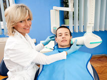 Woman dentist with male patient Stock Photos