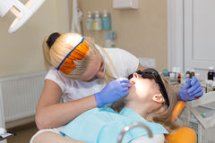 Woman dentist in mask treating her patient Royalty Free Stock Images