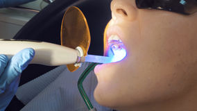 Woman at the dentist medical clinic for treatment. Woman at the dentist clinic office gets dental medical examination and treatment. Close up shot. Odontic and royalty free stock image