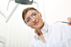 Woman dentist in protective glasses with mirror. Beautiful woman dentist in protective glasses ready to examine the patient Royalty Free Stock Photo