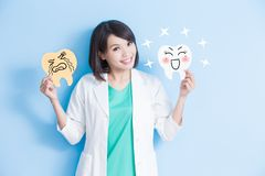 Woman dentist take tooth board. Woman dentist take decay and health tooth board on the blue background Royalty Free Stock Image