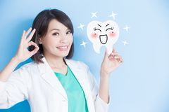 Woman dentist take tooth board. And show ok to you on the blue background Stock Images