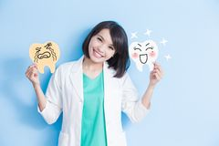 Woman dentist take tooth board. Woman dentist take decay and health tooth board on the blue background Stock Image