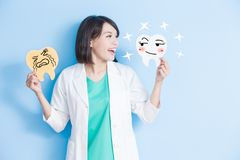 Woman dentist take tooth board. Woman dentist take decay and health tooth board on the blue background Stock Photos
