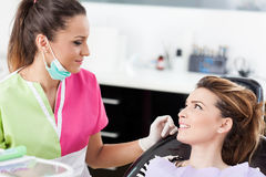 Woman dentist talking to her patient Royalty Free Stock Images
