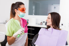 Woman dentist talking to her patient Stock Image