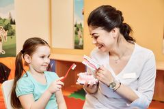 Woman dentist teaches little girl to brush her teeth royalty free stock image