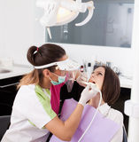 Woman dentist working with the driller Stock Photos