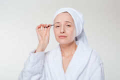 Woman depilating her eyebrow Stock Image