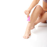 Woman depilating her legs Royalty Free Stock Image