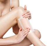 Woman depilating legs by waxing Royalty Free Stock Images