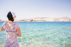 A woman deployed back dressed in a white tunic is seating in front the sea, she is watching an island royalty free stock photos