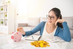 Woman deposit gold coin into piggy bank. Young mixed race asian woman deposit gold coin into piggy bank for future life sitting on sofa drinking coffee in the Stock Photos