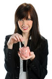 Woman Depositing Coin in Piggy Bank Royalty Free Stock Image