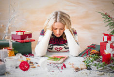 Woman depressed with Christmas gift clutter Royalty Free Stock Image