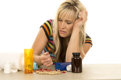 Woman depressed with hand full of pills eyes closed Royalty Free Stock Photography