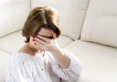 Woman with depression closes face with her hand Royalty Free Stock Image
