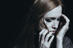 Woman with depression crying. Against black background with copy space stock photo