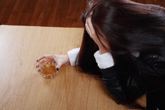 Woman in depression drinking alcohol. Young crying woman in depression drink drinking alcohol Dark tone image Stock Images