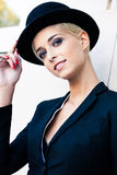 Woman with derby hat. Smiling elegant blonde short hair young woman wearing black tuxedo and derby hat portrait outdoor in the city stock images