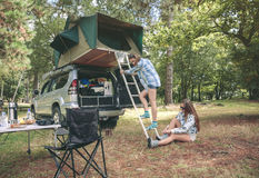 Woman descending ladder form tent over car. Young women descending ladder from tent over car while other women putting hiking boots sitting on the grass Stock Images