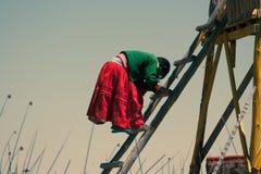Woman descending a ladder, Uros island, Titicaca Lake, Peru royalty free stock image