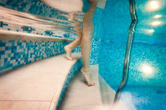 Woman descending the stairs in the pool Stock Image