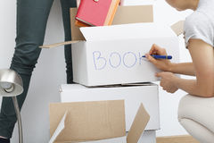 Woman descripting boxes. Woman descripting white boxes before moving out Stock Photo