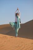 Woman in desert. Woman doing Yoga tree pose in desert dunes Stock Photos
