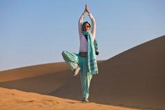 Woman in desert. Woman doing Yoga tree pose in desert dunes Royalty Free Stock Photo