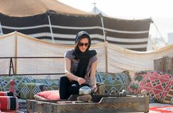 Woman in a desert camp near Doha. Woman in black makes tea in a desert camp near Doha, Qatar Stock Photos