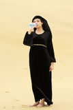 Woman in desert drinking water from bottle Royalty Free Stock Image