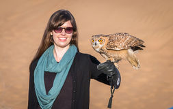 Woman with a desert eagle owl on her arm Royalty Free Stock Photo