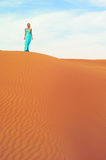 Woman and desert. UAE. Beautiful blonde in a blue dress in an orange desert. UAE Stock Photography