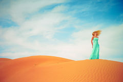 Woman and desert. UAE. Beautiful blonde in a blue dress in an orange desert. UAE Stock Image