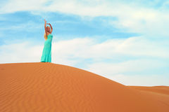 Woman and desert. UAE. Beautiful blonde in a blue dress in an orange desert. UAE Royalty Free Stock Image